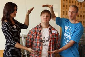 """tre ungdomar gestaltar """"museum"""" genom att visa en man som sitter i en monter"""